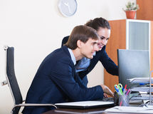 Two young managers using laptop at work Royalty Free Stock Photo