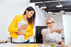 Two young and mature office women having a brainstorm meeting. Two pretty young and mature office women having a brainstorm meeting at the table in the office Stock Images