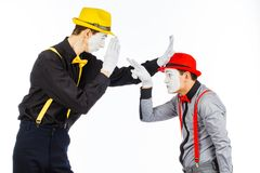 Two young men, an actor, a MIME, in clothing and makeup, argue, Stock Image