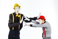 Two young men, an actor, a MIME, in clothing and makeup, argue, Royalty Free Stock Image