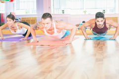 Two young men and asian girl doing pushups indoor Royalty Free Stock Images