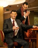 Two young men behind gambling table Stock Images