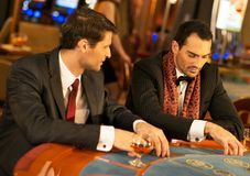 Two young men behind gambling table Royalty Free Stock Photos