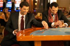 Two young men behind gambling table Stock Image