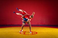 Two young men wrestling. Two young men in blue and red wrestling tights are wrestlng and making a hip throw on a yellow wrestling carpet in the gym Stock Photos