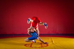 Two young men wrestling. Two young men in blue and red wrestling tights are wrestlng and making a hip throw on a yellow wrestling carpet in the gym Royalty Free Stock Photos