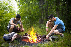 Two young men camping next to burning campfire Royalty Free Stock Photos