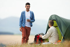 Two Young Men On Camping Trip In Countryside. Talking to each other stock images