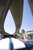 Two young men by car beneath overpass, smiling, portrait, low angle view Stock Image