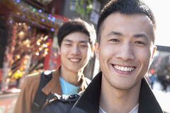 Two young men with Chinese Architecture in background. Stock Photo