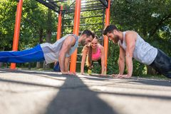 Two young men clapping hands from plank position during partner workout. Two fit young men clapping hands from face to face plank position during partner workout royalty free stock image