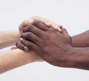 Two young men clasping each others hands, close-up, studio shot Royalty Free Stock Photography