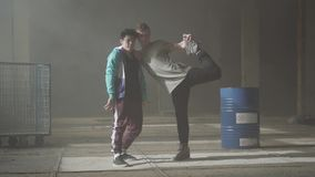 Two young men dancing in the dark and dusty room of abandoned building. The guys making dance moves and poses, looking stock footage