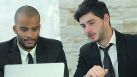 Two young men discussing information on the laptop. Smiling businessman in a meeting. Business meeting with colleagues. Four smiling successful businessmen stock video