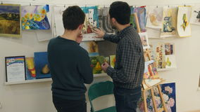 Two young men discussing paintings drawn by art students stock footage