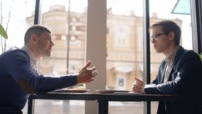 Two young men are discussing startup, sitting at table in cafe, businesspeople sharing ideas, talking, having. Conversation about new project by window in stock footage