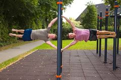 Two young men doing calisthenics exercises on bar outdoors stock photo