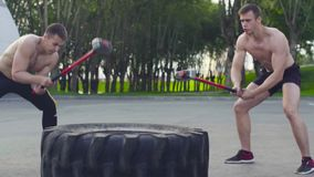 Two young men doing exercises on a large wheel and hammer. Outdoors stock footage