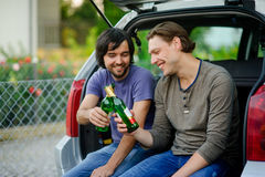 Two young men drink beer from bottles. Stock Photography