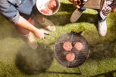 Two young men drinking beer and grilling burgers outdoors Stock Images