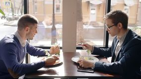 Two young men are eating and talking, sitting at table in cafe. Two young men are eating and talking, sitting at table in cafe, handsome guys is in dialogue stock footage