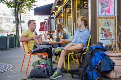 Two young men enjoying glass of beer in cafe in Paris Stock Photography