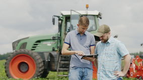 Two young men of the farmer communicate, use the tablet. Stand in the field against a tractor background. HD video stock video