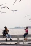 Two young men feeding birds in the air at Bang Pu seaside. Royalty Free Stock Images