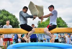 Two young men fight for fun in a battle of sacks during Sabantui