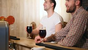 Two young men friends sitting in bar and talking with each other while drinking beer.  stock video