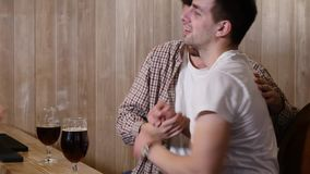 Two young men friends sitting in bar and talking with each other while drinking beer. Two young men friends sitting in bar and talking with each other while stock video