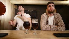 Two young men friends sitting in bar and talking with each other while drinking beer. Two young men friends sitting in bar and talking with each other while stock footage