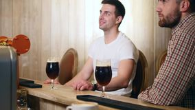 Two young men friends sitting in bar and talking with each other while drinking beer.  stock footage