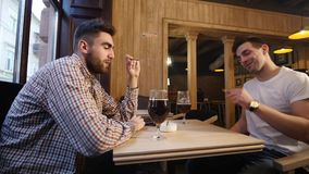 Two young men friends sitting in bar and talking with each other while drinking beer. Two young men friends sitting in bar and talking with each other while stock video footage