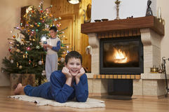 Two young men front of fireplace at Christmas Royalty Free Stock Image