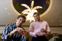 Two young men with gambling chips, portrait, low angle view Stock Photo