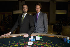 Two young men gambling at poker table, smiling, portrait Stock Photography