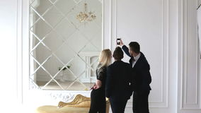 Two young men and a girl making a selfie, laughing and turning. The handsome men are in suits. The pretty girl is in a black dress. She has long blond hair stock footage