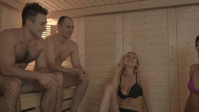 Two young men and girls relaxing in the sauna. Four friends are talking with each other. The camera moves from men to girls. Two attractive men and two young stock video footage