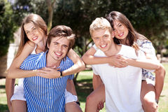 Two young men giving her lover piggy back in park Stock Photography
