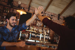 Two young men giving high five to each other. In pub Stock Photo