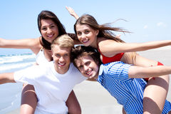Two young men giving piggy back to his women Royalty Free Stock Images