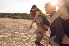 Two young men giving their girlfriends piggyback rides Royalty Free Stock Image