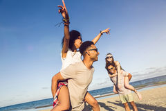 Two young men giving their girlfriends piggyback rides Stock Photography