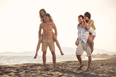 Two young men giving their girlfriends piggyback rides at the beach Stock Photography