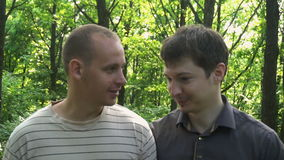 Two young men go through the woods and talking stock video footage