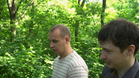 Two young men go through the woods and talking stock video