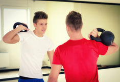 Two young men in gym working out with kettlebells Royalty Free Stock Photo