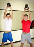 Two young men in gym working out with kettlebells Royalty Free Stock Image