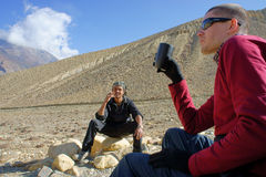 Two young men have a rest sitting on the rocks in the mountain. S, and tourist guide. Nepal Stock Photo